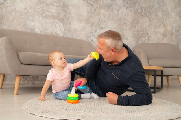 Little girl collects a pyramid with grandparents at living room. grandfather plays with granddaughter on the floor near sofa. the child feeds a toy duck to the grandpa