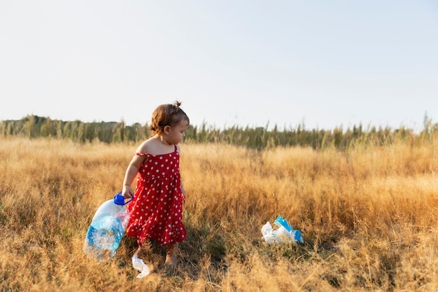 Little girl collects trash scattered in the forest.