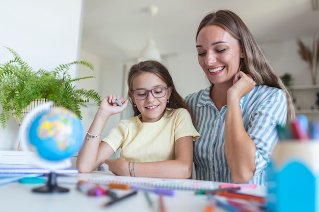 Little girl coloring picture in album during staying at home with mother, widescreen. generation and happy family concept