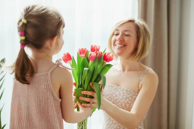 Маленькая девочка поздравляет ее мать и дарит ей цветы. с днем матери! мама и дочь улыбаются и проводят время вместе. сосредоточьтесь на тюльпанах.