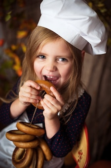 Little girl in cook clothes with bagels in her hands and smiling