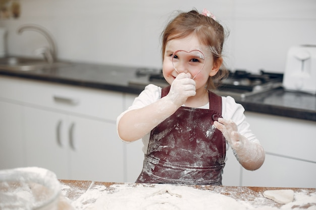 Little girl cook the dough for cookies