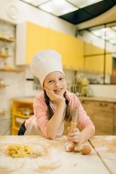 小さな女の子はキャップとエプロンで調理し、キッチンで混合、クッキーの準備のために泡立て器を保持します。ペストリーを調理する子供たち、ケーキを準備する子供たちのシェフ