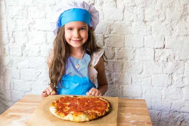 Маленькая девочка повар улыбается возле пиццы пепперони в форме сердца после приготовления.