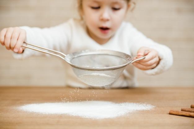 Маленькая девочка готовит на кухне