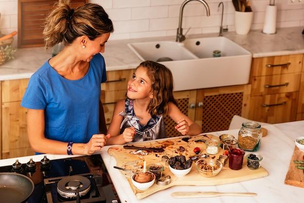 Маленькая девочка готовит с матерью на кухне. концепция младенческого шеф-повара.