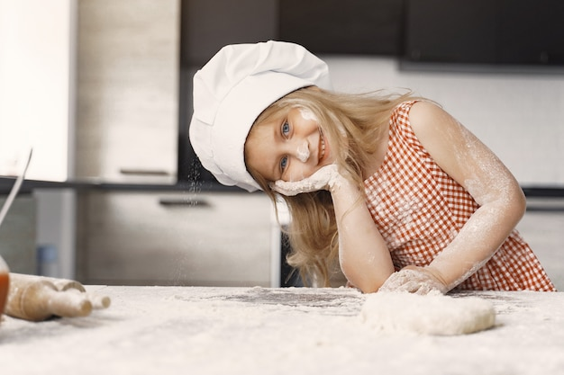 Little girl cooks the dough for cookies