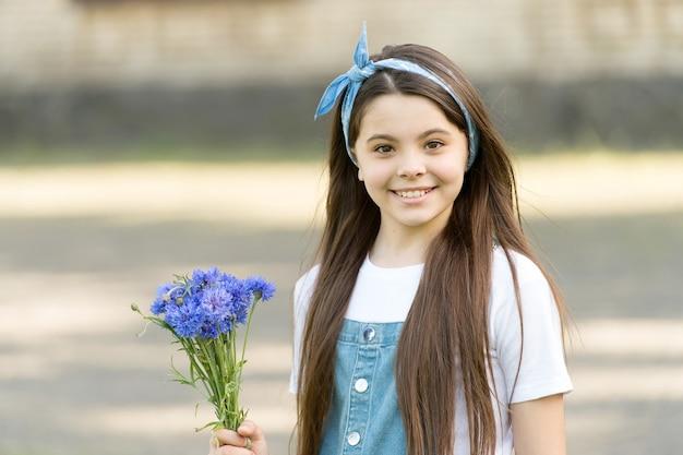 小さな女の子のヤグルマギクの花束の休日の挨拶、誕生日プレゼントのコンセプト。