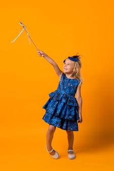 Little girl in costume with wand and mask
