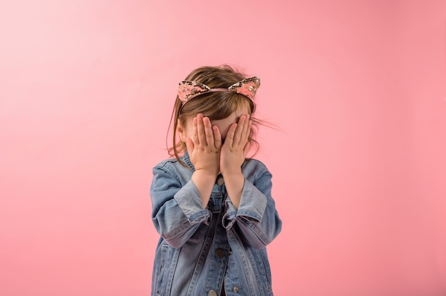 The little girl covered her face with her hands against the pink space. upset girl with loose hair on the head of the band with the ears of a cat.