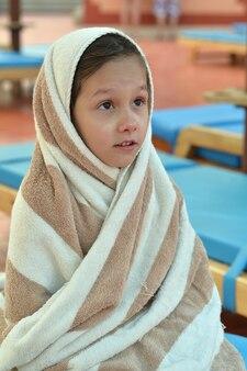 수영장 근처 수건으로 덮인 어린 소녀
