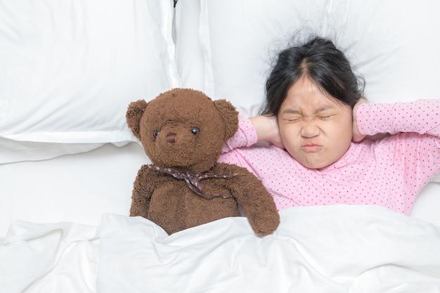迷惑な大きな音を無視して耳を覆っている少女は、ベッドで音が聞こえないように耳をふさいでいます。ヘルスケアの概念