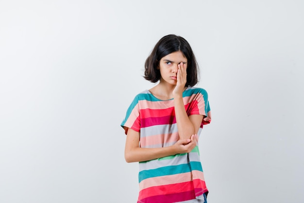 Bambina che copre l'occhio con la mano mentre tiene la mano sul gomito, distoglie lo sguardo in maglietta e sembra assonnata, vista frontale.