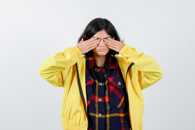 Маленькая девочка закрыла глаза руками в клетчатой рубашке, куртке и выглядела мило. передний план.