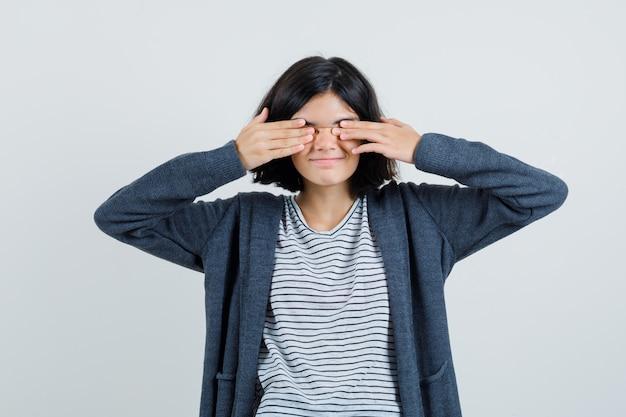 T- 셔츠, 재킷에 손으로 눈을 덮고 흥분 찾고 어린 소녀.