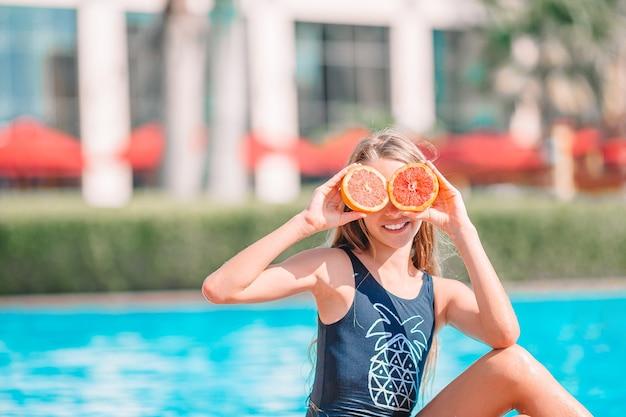 スイミングプールの目の近くにレモンの半分で目を覆っている少女