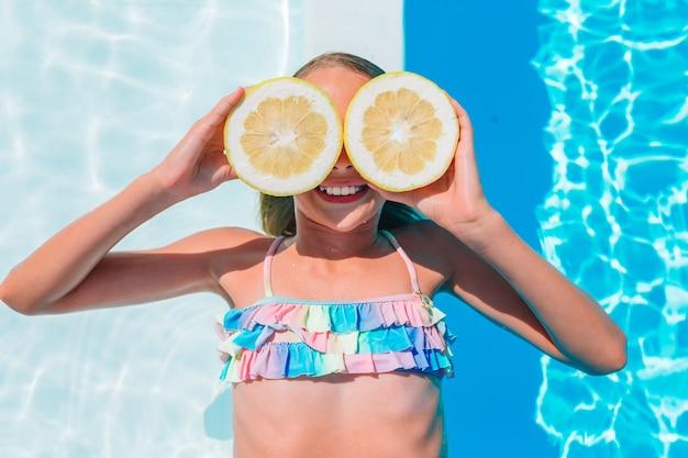 Little girl covering eyes with lemon halves near eyes on swimming pool