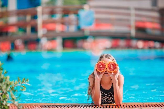 背景のスイミングプールの目の近くにオレンジ色の半分で目を覆っている少女
