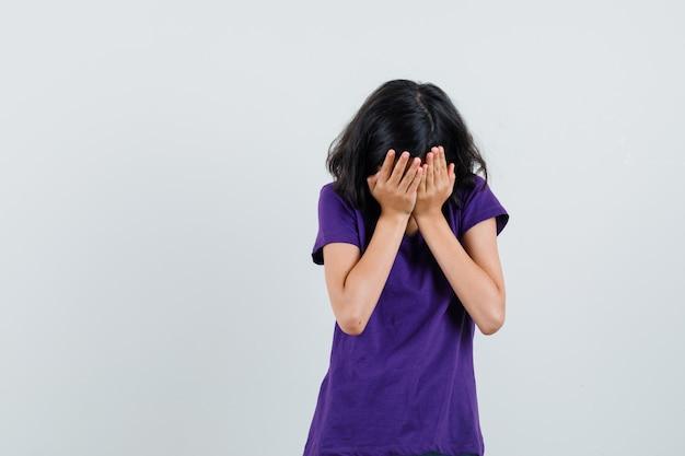 어린 소녀는 t- 셔츠에 손으로 얼굴을 덮고 고뇌보고,