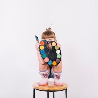 Little girl covering face with palette on chair
