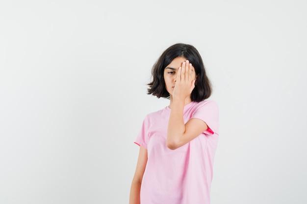 Bambina che copre metà del viso con la mano in maglietta rosa, vista frontale.