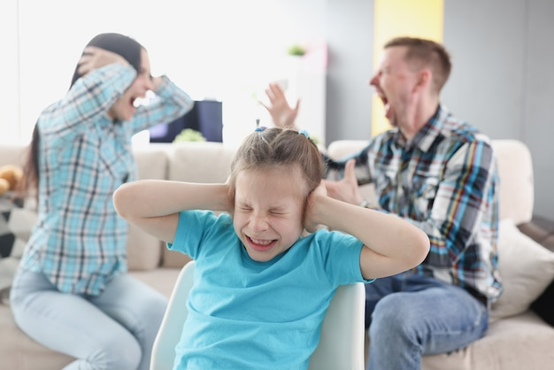 Little girl covering her ears with her hands against background of swearing parents at home
