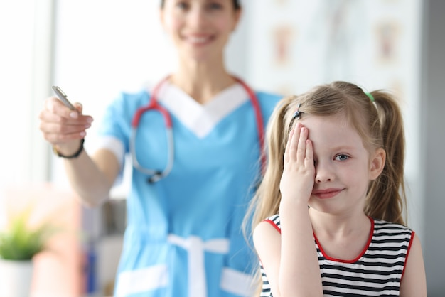 Маленькая девочка закрыла глаза рукой на приеме у офтальмолога