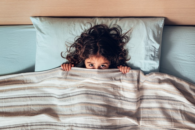 Little girl covering her face with the bedspread