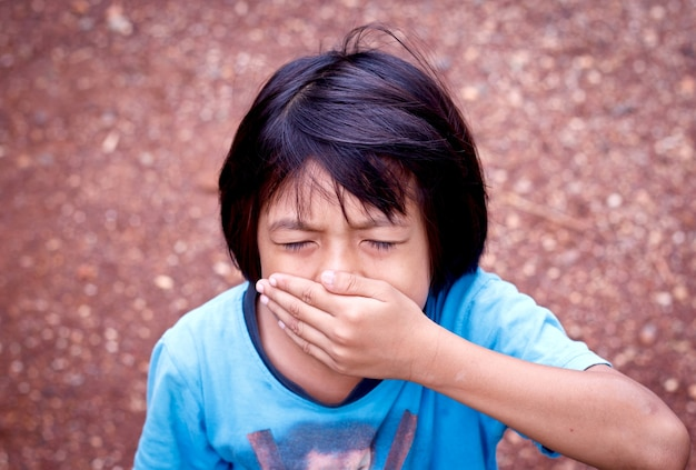 Little girl covering her mouth with her hand.