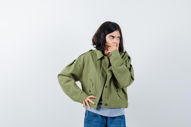 Little girl covering mouth with hand in coat, t-shirt, jeans and looking amazed. front view.