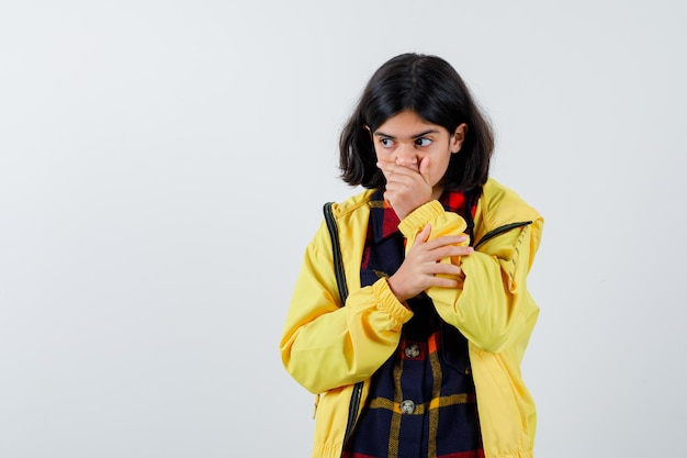 チェックのシャツ、ジャケットで手で口を覆い、驚いて見える少女。正面図。
