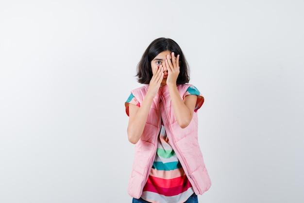 小さな女の子が手で顔の一部を覆い、tシャツ、フグベスト、ジーンズで頬に片手を持って怖がっています。正面図。