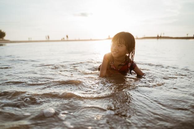小さな女の子が水で遊んでいる間、ビーチの砂の上をクロールします。