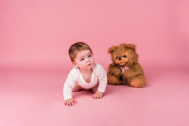 Маленькая девочка ползет рядом с плюшевой игрушечной собакой