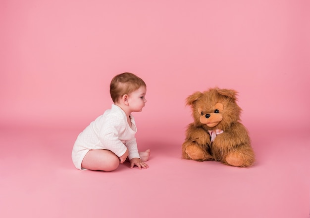 Little girl crawling next to a plush toy dog