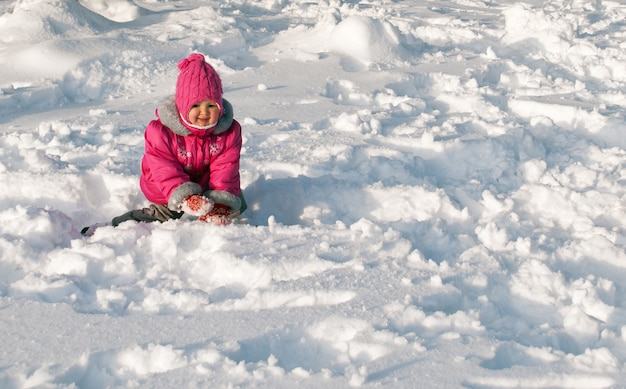 Little girl crawling on the snow