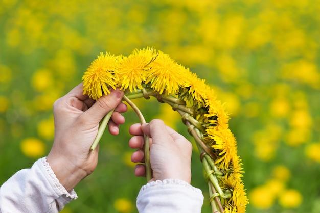 신선한 노란 민들레에서 꽃 화 환을 만드는 어린 소녀. 꽃으로 수공예품.