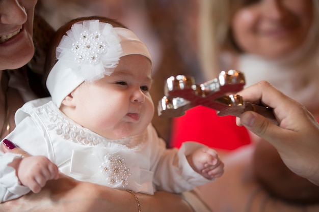 To a little girl and a cross at the ceremony of baptism.baptizing a child