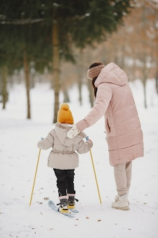 Little girl cross-country skiing with her mother