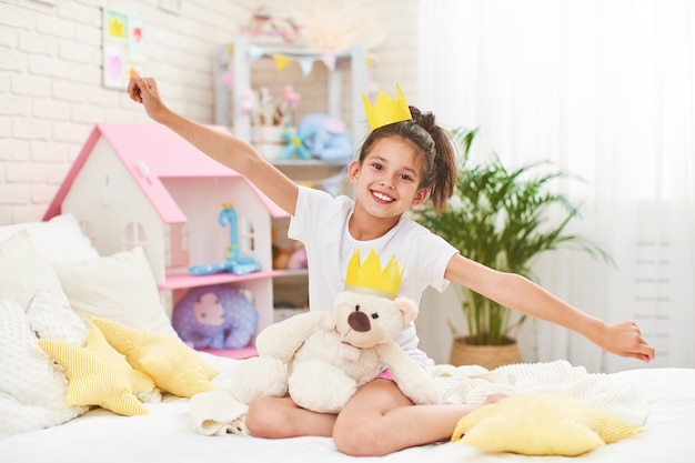 Little girl in crown, sitting on bed in children's room and hugging teddy bear