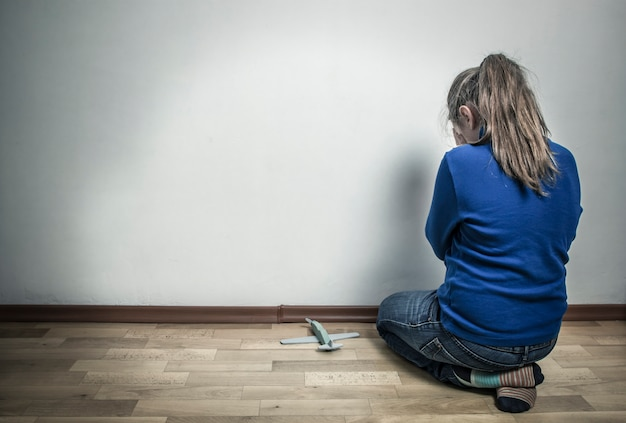 Little girl crying while sitting in an empty room. the child is offended. autism