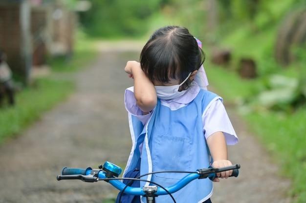Маленькая девочка плачет, сидя на велосипеде на дороге на открытом воздухе.