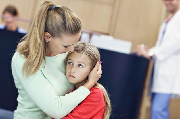상담 의사에서 그녀의 어머니와 함께 우는 어린 소녀