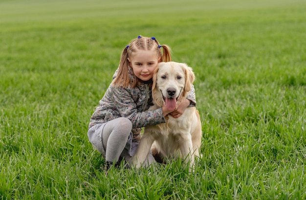 Little girl cuddling dog on field