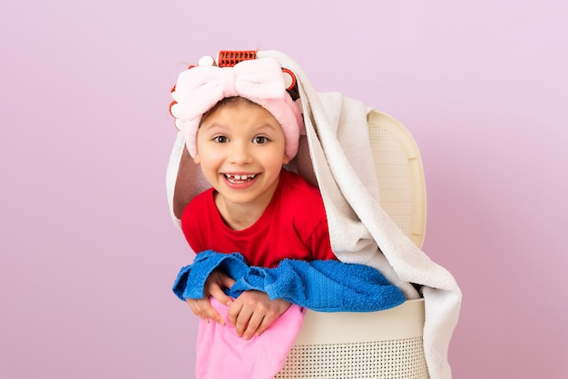 A little girl in curlers is going to wash dirty things. laundry and dry cleaning.