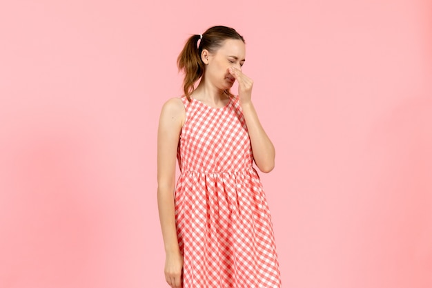 Bambina in abito luminoso carino che copre il naso in rosa