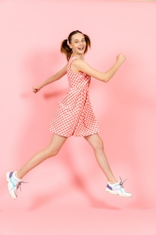Little girl in cute bright dress jumping happily on pink