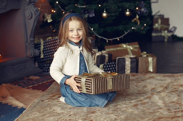 Little girl in a cute dress near christmas tree with present