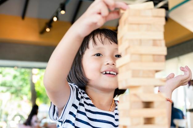 小さな女の子かわいい子供はジェンガ木製ブロックゲームをプレイしています。楽しんで創造性を学ぶ