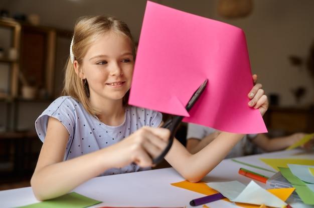 Маленькая девочка режет цветную бумагу за столом, ребенок в мастерской. урок творчества в художественной школе. молодой художник, приятное хобби, счастливое детство